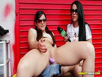 Brunette chick plays with a dildo in public