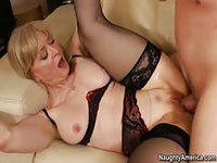 Mature blonde gets fucked over counter-top then moves to the couch for more fun