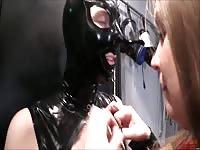 Lesbian dominatrix plays with her masked PVC sluts tits