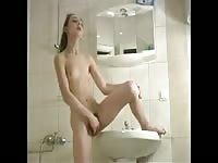 Sexy Russian schoolgirl enjoys masturbating her wet pussy in the bathroom